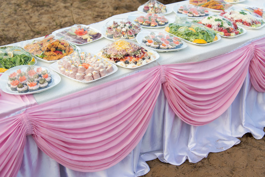 Buffet catering for a wedding party on the beach on a white table with a pink drapery