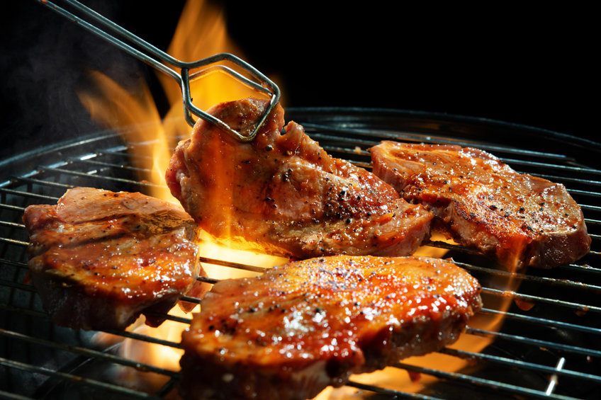 pork steaks on barbecue grill with flames