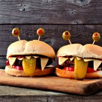 Halloween monster hamburgers on a paddle board against an old wood