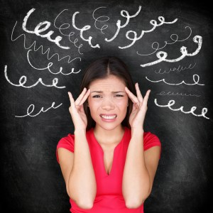 Stress - woman stressed with headache. Female stressed and worried with migraine headache pain. Blackboard concept with young female model on chalkboard black background. Asian Chinese / Caucasian.