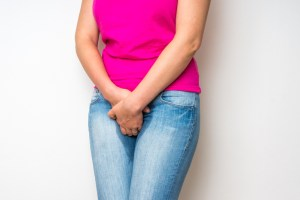 woman holding crotch due to urinary problem