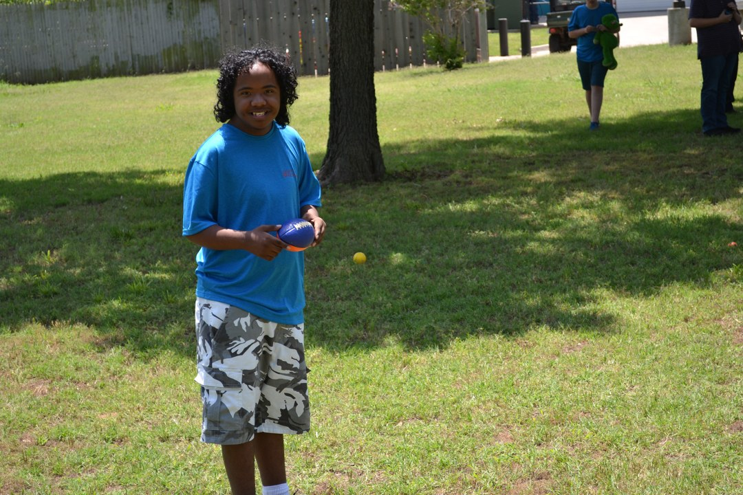A camper holds a football during field day at Camp Tumbleweed.