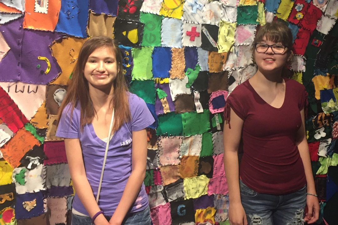 Campers at a quilt wall