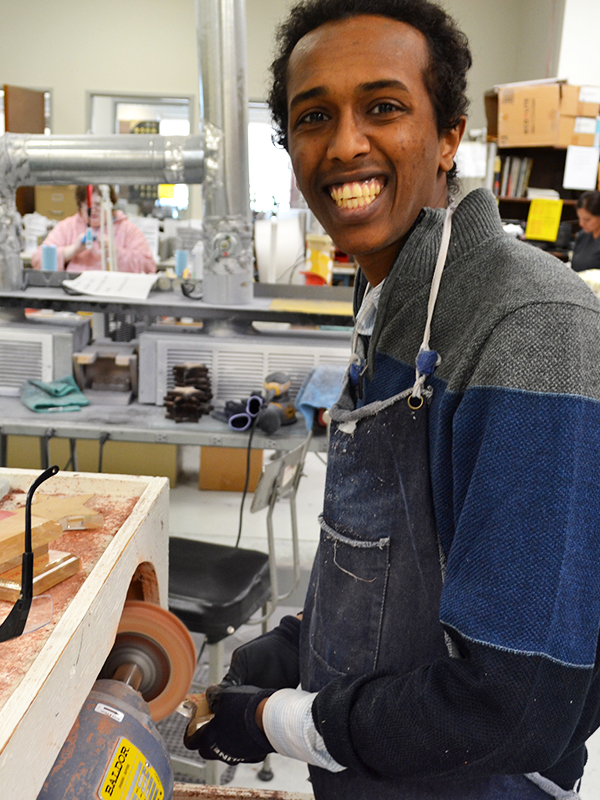 Joshua smiling while buffing an acrylic award at Prism Place.