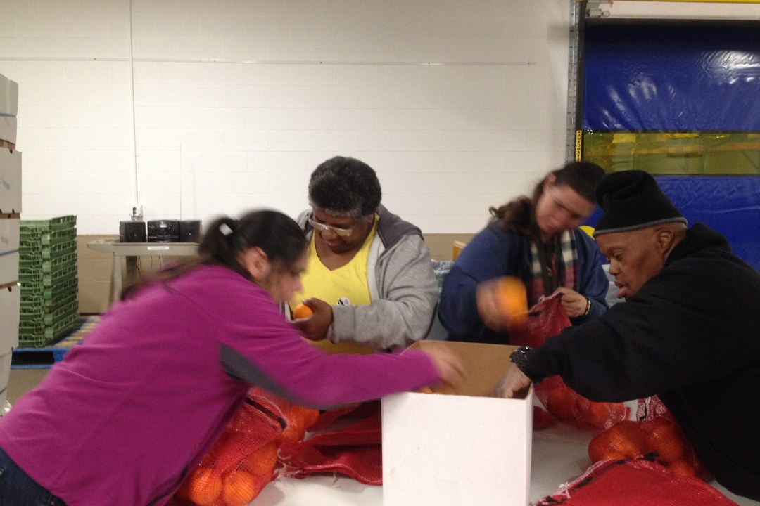 A group of individuals volunteering at the Regional Food Bank of Oklahoma sorting food.