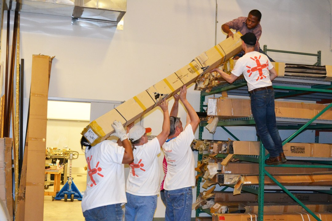 Volunteers with OG&E lift a large box onto a shelf at DRTC.