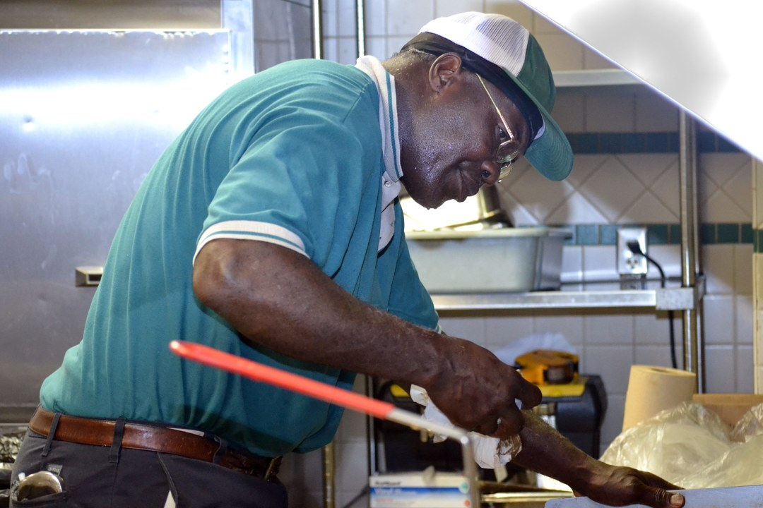 A cook prepares food at DRTC's Food Service contract at Tinker Air Force Base.