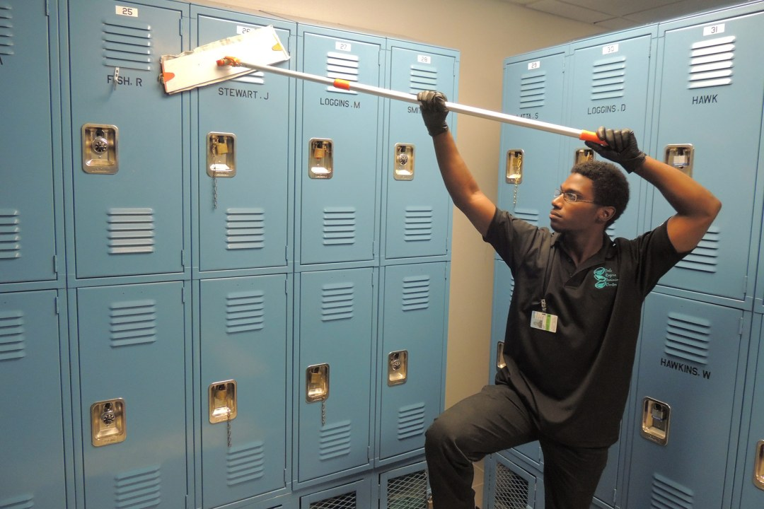 A custodial team member cleans the outside of lockers.