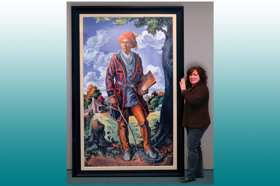 Carla standing next to an 8' tall framed image of Chief Sequoyah.