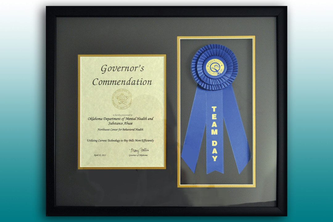 Framed Governor's Commendation with blue ribbon.