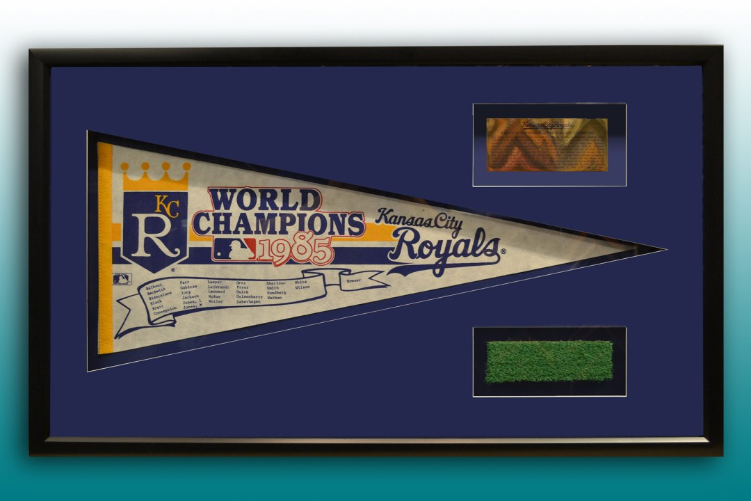 Framed 1985 Kansas City Royals pennant and turf cutout.
