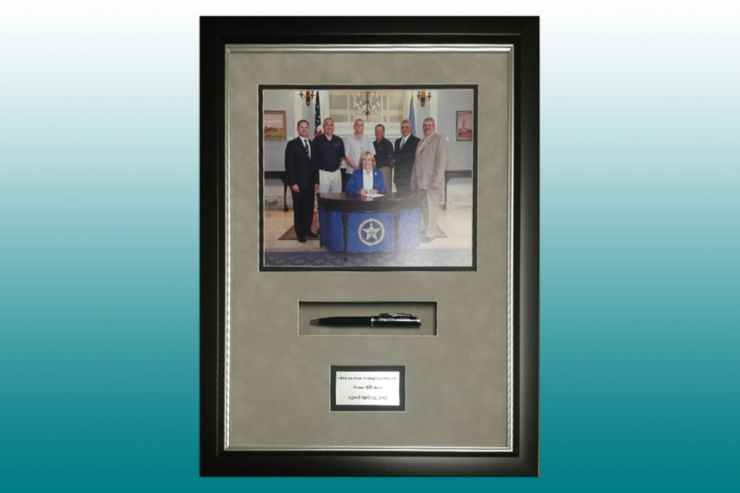 Picture of Governor Fallin at a bill signing, along with an inset pen framed at DRTC Picture Frames.