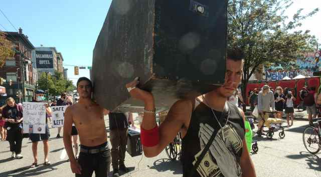 Two men carry a large black wooden coffin along the march route