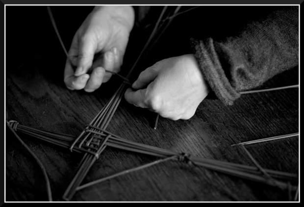 On voit deux mains qui font un noeud pour attacher une branche de croix de Brigantia posée sur une table.