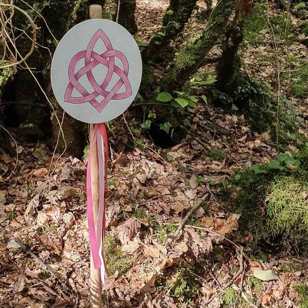 Il y a un panneau circulaire marqué d'un symbole pour honorer la Déesse Aliya, des rubans roses sont suspendus à l'occasion des célébrations druidiques de Dagdia.
