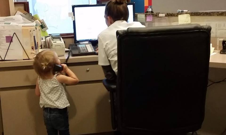 Small child answering phone at desk