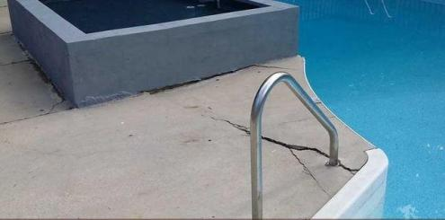 Cracked pool deck before concrete leveling