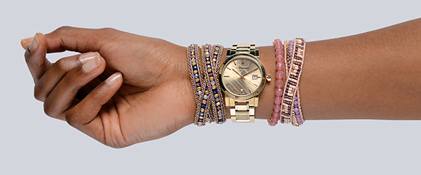 Nakamol purple and rose gold multiple-wrap woven bracelet ($47 at Von Maur). Burberry gold watch with check pattern face in gold ($695 at Von Maur). Alex and Ani blush Bohemian jewel bracelet ($38 at Von Maur). Nakamol purple and gold multiple-wrap woven bracelet ($40 at Von Maur).