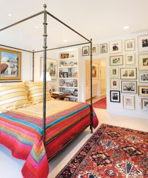 "In the master bedroom, a metal canopy bed takes center stage when covered with bed linens from India and pillows from a Des Moines Art Center ""Arts and Ends"" sale. Built-in shelves display books, collectibles and family heirlooms, while an adjacent photo wall showcases generations of Gallagher's family."