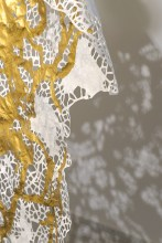 """Detail from one of Running's """"Predator"""" sculptures. To create this work, Running drew and then hand-cut the lacy design in the paper, finishing it with gold auto body paint and coyote pelt scraps from the garment industry (the fur isn't seen in the detail). The """"Predator"""" works represent the skin and fur of animals that used to prey on deer but don't any longer, allowing Iowa's deer herds to multiply."""