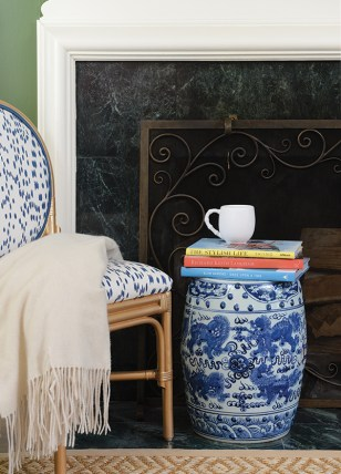 Along with the mantel, the fireplace's hearth, surround and grate should be considered when making decor decisions. Here, interior designer Amanda Reynal used a blanket, rug and upholstered chair to provide a soft contrast to the hard surfaces of the fireplace, creating a look that's both artful and inviting.