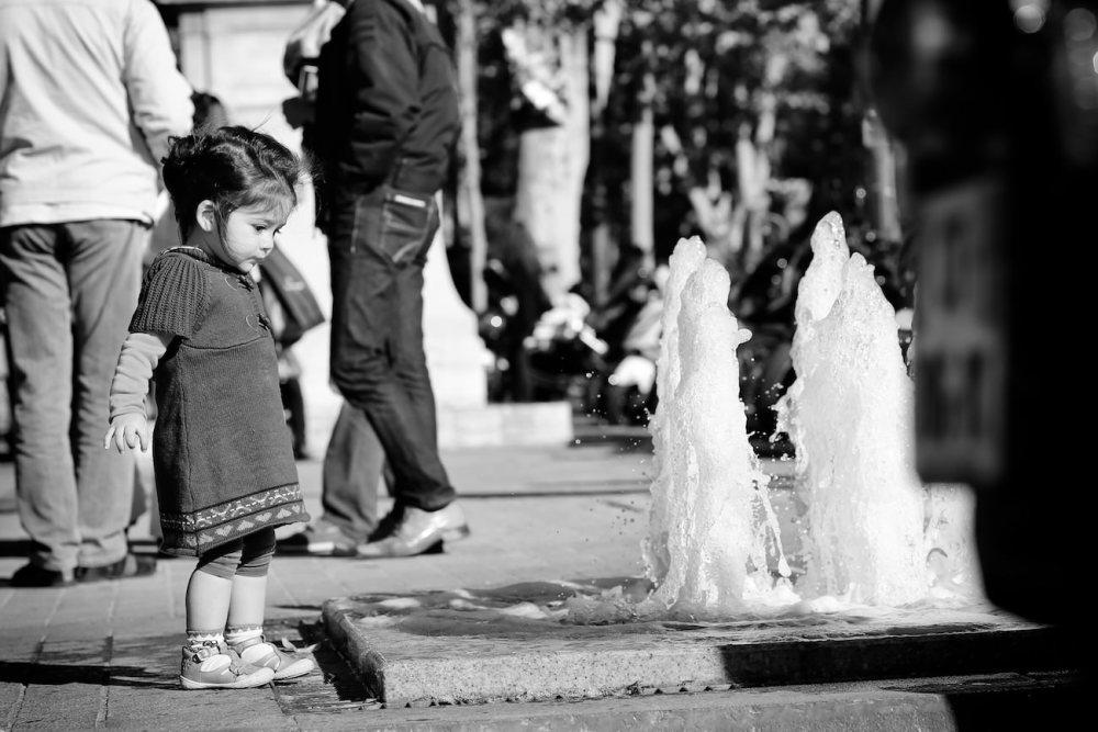Photo d'une fille qui regarde la fontaine