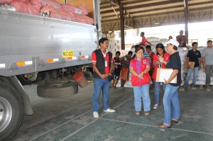(Center) DSWD Sec. Dinky thanks USAID through their Area Team Leader Ainee Amboy (right) for the three truckloads of relief goods donated by USAID that were brought to the DPWH warehouse for repacking.