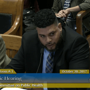 Duane testifying at a legislative hearing on domestic violence as public health issue.
