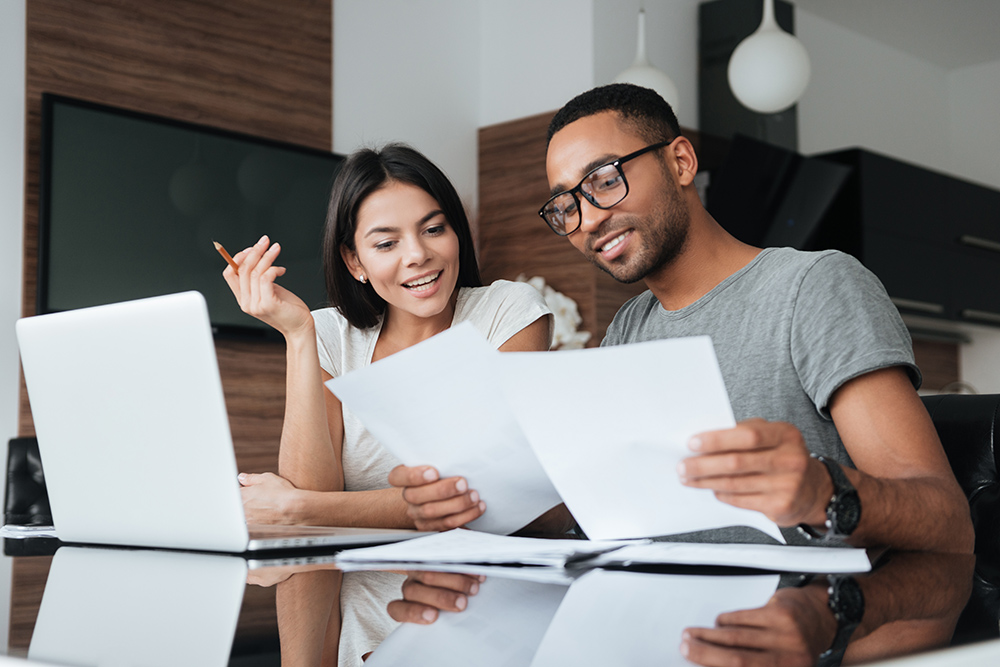 Couple looking over paperwork with laptop