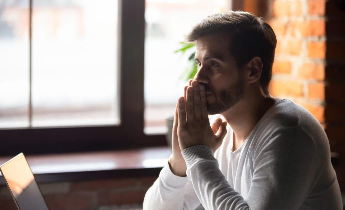 Man thinking whilst sat at desk with laptop at work