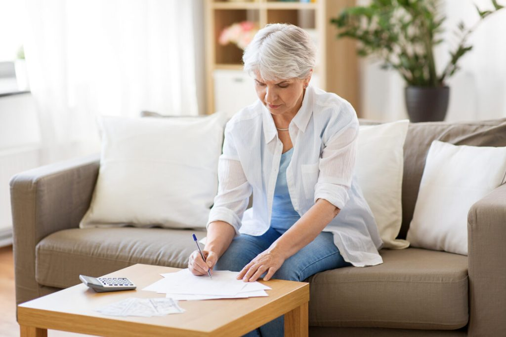 Mature women looking at paperwork with calculator