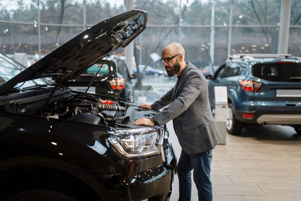 Customer on his own at car dealership, car showroom