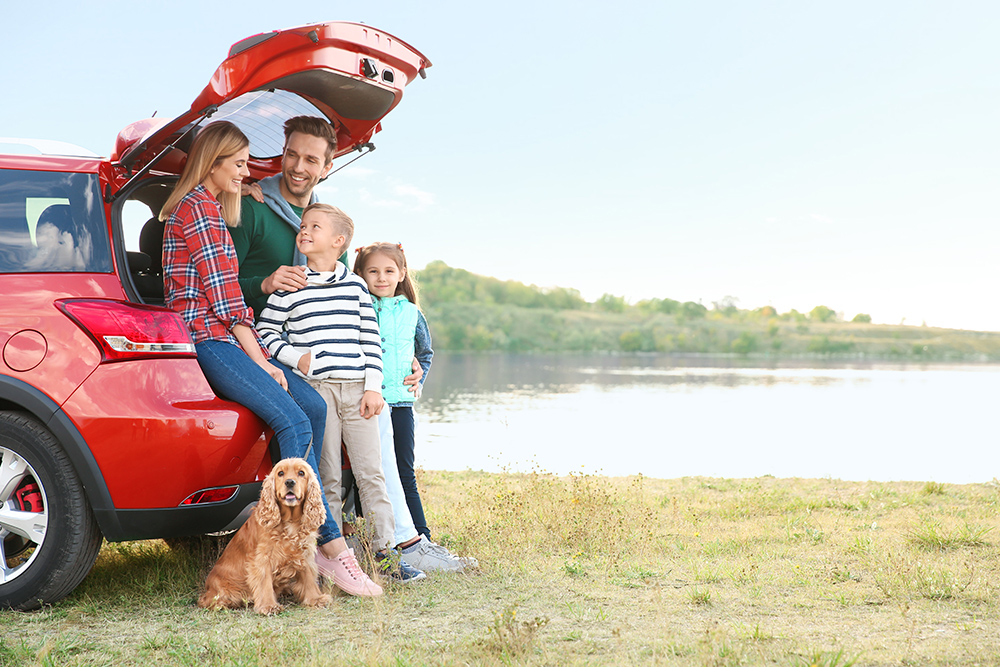 Family and dog stood by car on holiday by lake.