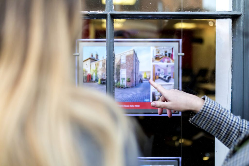 Couple looking at a property advert in the window of an estate agents.