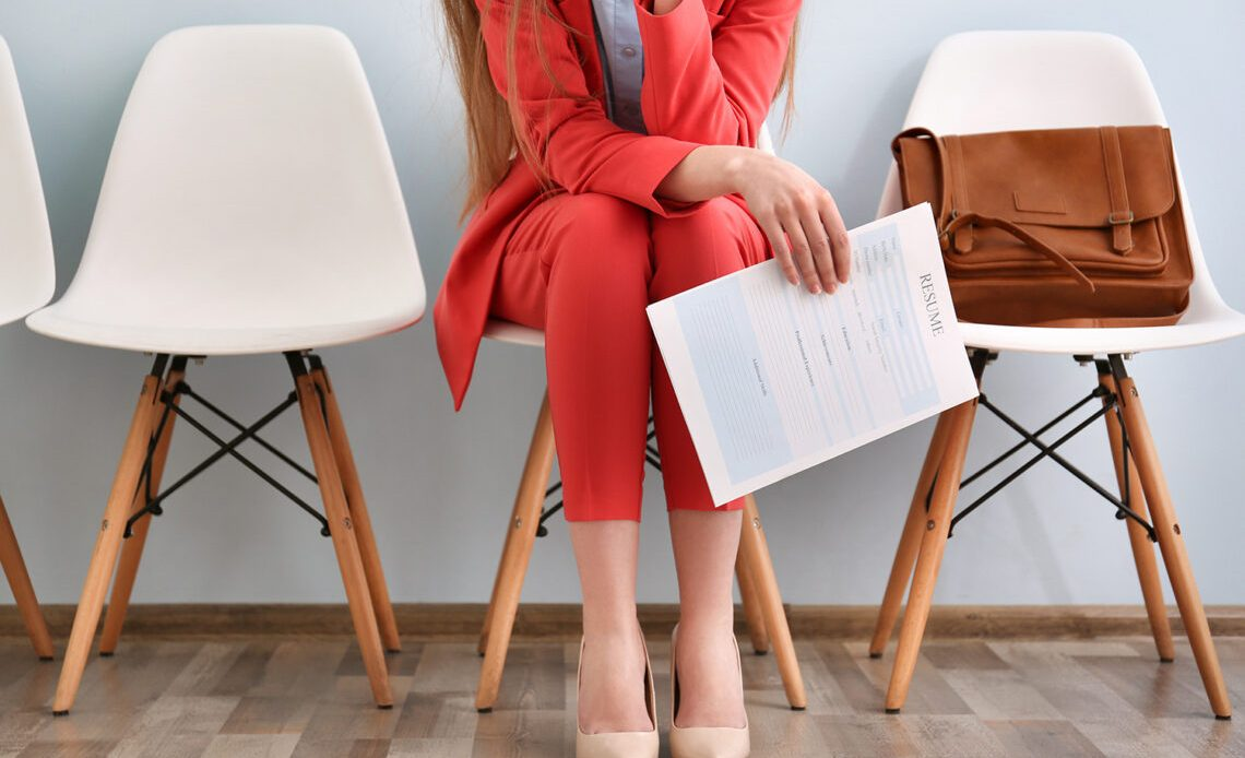 Women in red suit waiting for job interview
