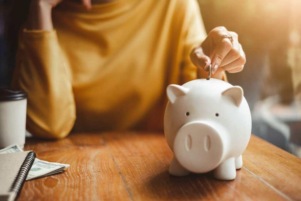 Depositing money in piggy bank