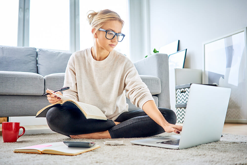 Women with glasses on, sat on floor with laprop and calculator