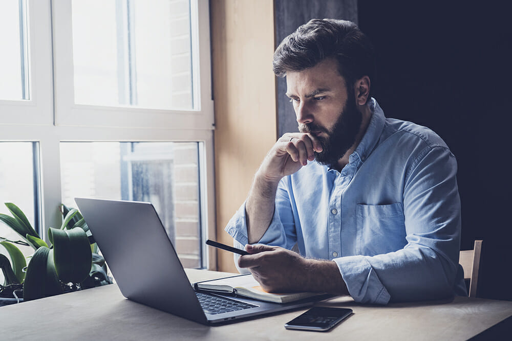 Man thinking whilst looking at mobile phone and laptop