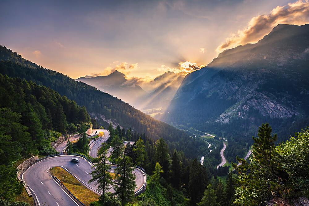 Driving in Europe - Maloja Pass road in Switzerland at sunset