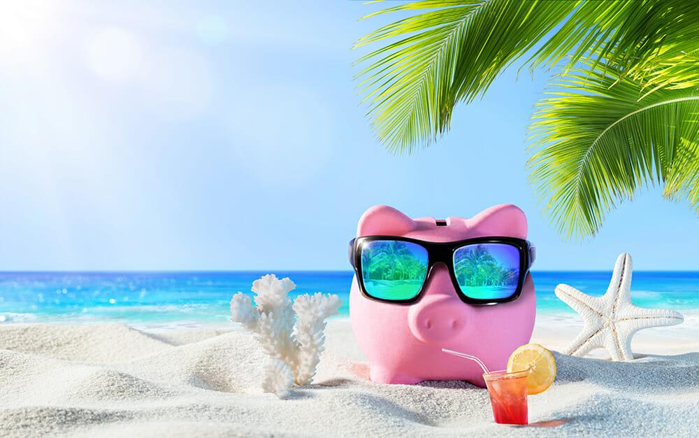 Piggy bank with sunglass on a tropical beach