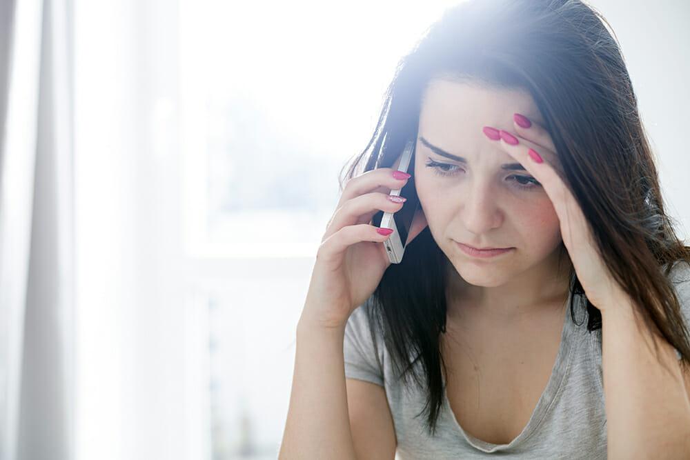 Women using phone looking worried