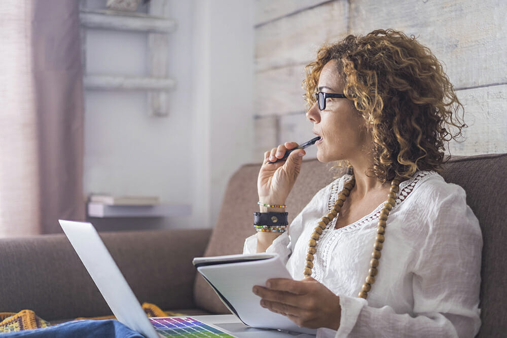 Women thinking with note pad, pen and laptop