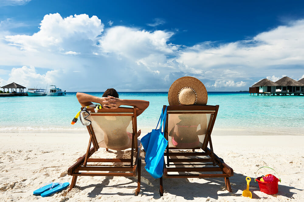 Couple sitting on deck chairs on beach holiday