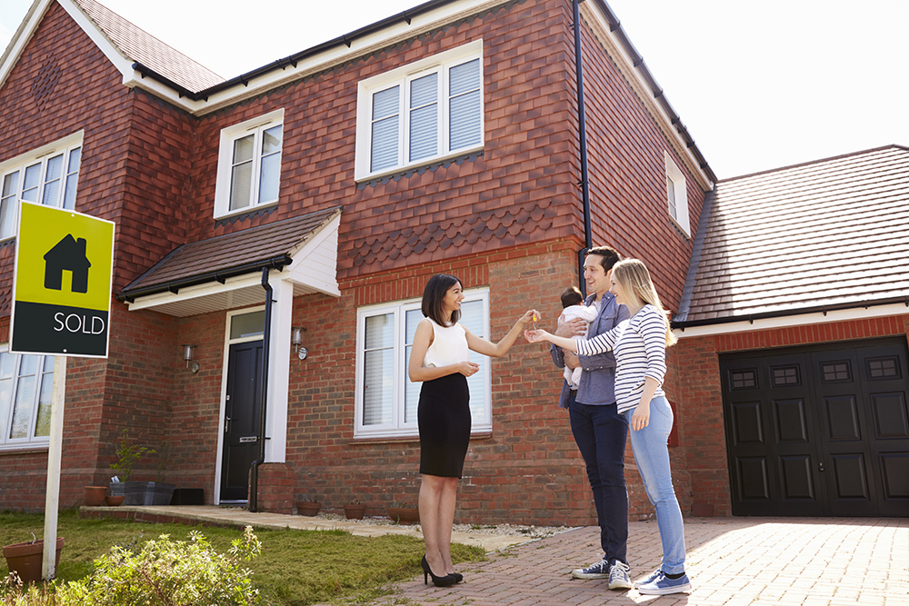Couple with baby receiving keys from estate agent. Buying new home.