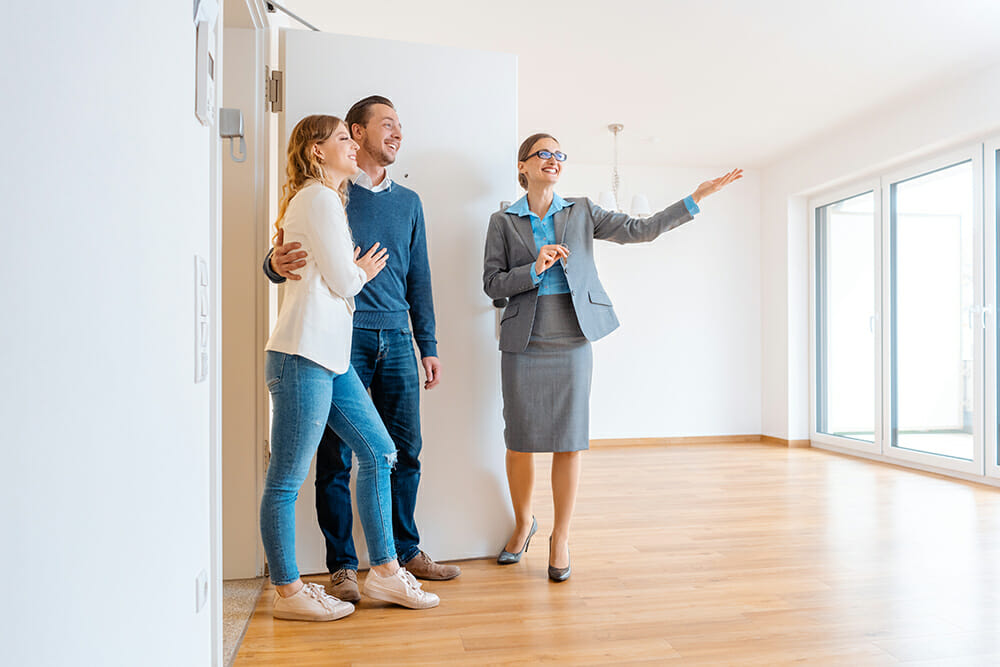 Estate agents showing couple around rental property