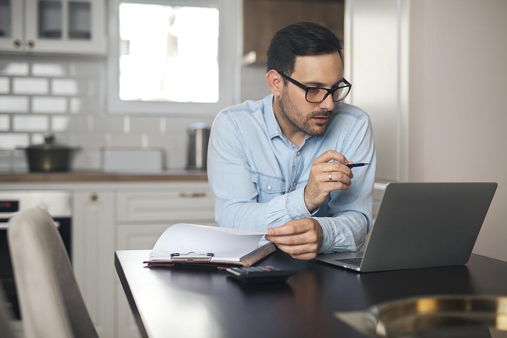 Man looking at laptop. Using calculator.