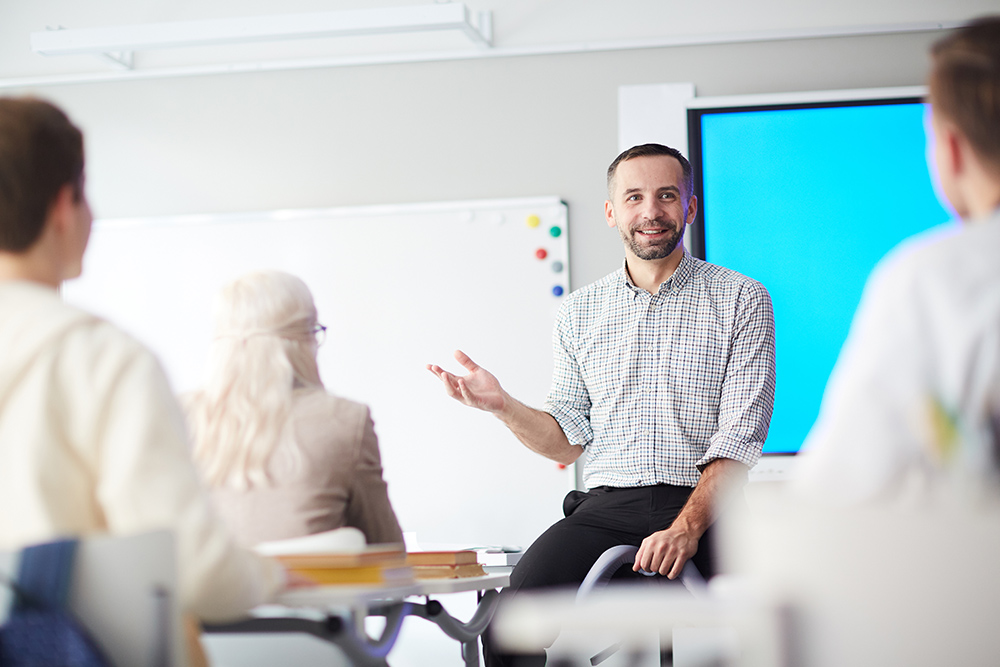 Man teaching adult education in class room