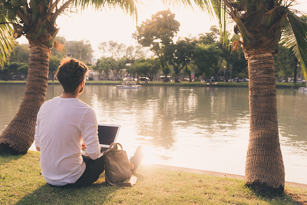 Young man sitting by lake and palm trees working on laptop