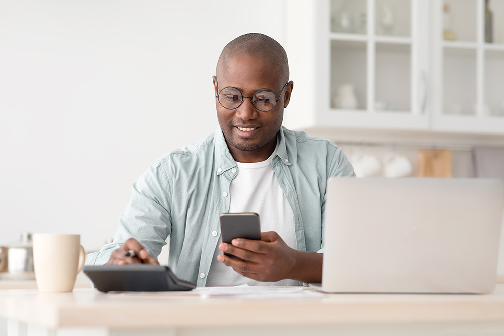 Man sat at desk with laptop calcultor and smart phone