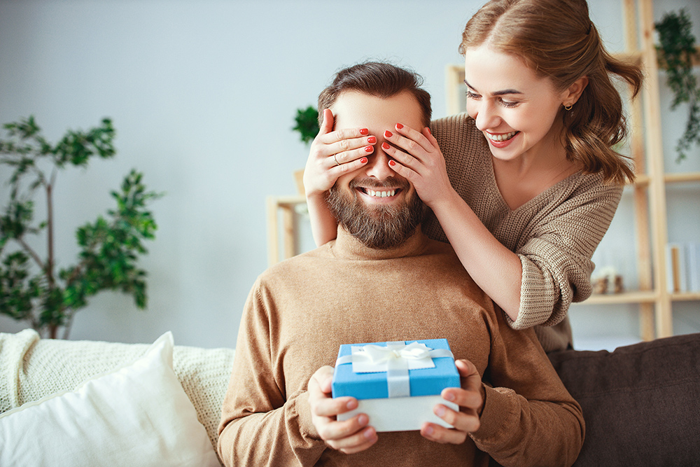 Women covers mans eyes and man holds surprize gift box